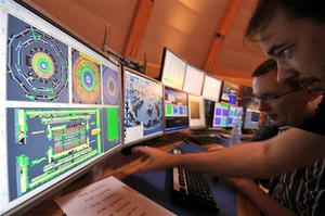 European Center for Nuclear Research (CERN) scientists control computer screens showing traces on Atlas experiment of the first protons injected in the Large Hadron Collider (LHC) during its switch on operation at the Cern's press center on Wednesday, Sept. 10, 2008 near Geneva, Switzerland. Scientists fired a first beam of protons around a 27-kilometer (17mile) tunnel housing the Large Hadron Collider (LHC). They hope to recreate conditions just after the so-called Big Bang. The international group of scientists plan to smash particles together to create, on a small-scale, re-enactments of the Big Bang. (AP Photo/Fabrice Coffrini, Pool)
