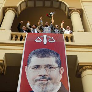 Supporters of the Muslim Brotherhood's candidate, Mohammed Morsi, celebrate above a giant poster of him (AP)