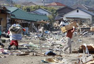 Residents of the seaside town of Toyoma, northern Japan, carry belongings from their homes Monday, March 14, 2011, three days after a giant quake and tsunami struck the country's northeastern coast. (AP Photo/Mark Baker)