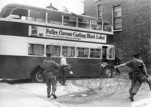 Riots : Belfast. August 1969.  Corporation workmen guarded by troops remove the barricade at Herbert Street while engineers arrive to retrieve a bus used as a barricade.  (19/8/69)