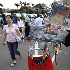 Chinese tourists pass Taiwanese souvenirs as they arrive at the Sun Yat-sen Memorial Park in Taipei, Taiwan (AP)