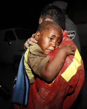 A Spanish rescuer carries two-year-old Redjeson Hausteen after he was rescued