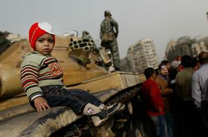 CAIRO, EGYPT - JANUARY 29:  A child sits on a tank while a Egyptian soldiers stands by during a demonstration against President Hosni Mubarek in Tahrir Square on January 29, 2011 in Cairo, Egypt. Tens of thousands of demonstrators have taken to the streets across Egypt in Cairo, Suez, and Alexandria to call for the resignation of President Hosni Mubarak. Riot police and the Army have been sent into the streets to quell the protests, which so far have claimed at least 38 lives and left more than a two-thousand injured. The cabinet has formally resigned, but protesters are seeking a regime change with the resignation of Mubarak. The government has installed a curfew, blockaded access to the Giza pyramids with tanks and APC's and taken measures to secure museums from looters.  (Photo by Chris Hondros/Getty Images) *** BESTPIX ***