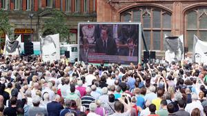 People watch Prime Minister David Cameron on a giant screen making a statement to the House of Commons regarding the findings of the Saville Inquiry into Bloody Sunday, outside the Guildhall