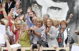 Relatives of those shot dead on Bloody Sunday wave to crowds after reading a copy of the long-awaited Saville Inquiry report, outside the Guildhall