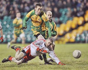 Kevin Hughes of Tyrone and Donegal's Edward Kelly battle for possession