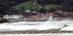 Surf crashes ashore at Sandsend, near Whitby, North Yorkshire, as fierce storms battered Britain today, with heavy rain and winds gusting up to 85mph