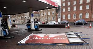 An advertising board lies on the ground in a petrol station in Glasgow city centre, as fierce storms battered Britain today, with heavy rain and winds gusting up to 85mph