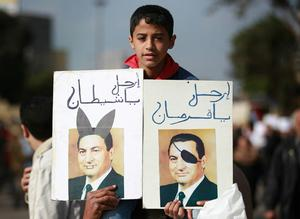 CAIRO, EGYPT - JANUARY 30:  A boy in Tahrir Square holds doctored photographs of President Hosni Mubarak on January 30, 2011 in Cairo, Egypt. As President Mubarak struggles to regain control after five days of protests he has appointed Omar Suleiman as vice-president. The present death toll stands at 100 and up to 2,000 people are thought to have been injured during the clashes which started last Tuesday. Overnight it was reported that thousands of inmates from the Wadi Naturn prison had escaped and that Egyptians were forming vigilante groups in order to protect their homes after Police were nowhere to be seen on the streets. Broadcasts from the Al-Jazeera television network via an Egyptian satellite have now been halted.  (Photo by Peter Macdiarmid/Getty Images)