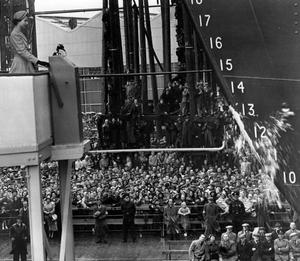 Thousands of eyes leave the Queen for a monemt as she pulls a lever, the swinging bottles smashes against the bow and the Southern Cross is launched at the Queen's Yard, Belfast.  17/8/1954