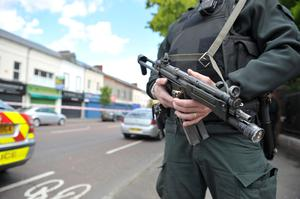 Armed PSNI officers at the scene of yesterday's fatal shooting on the Shankill Road
