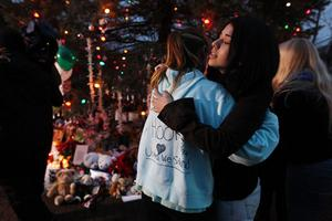 NEWTOWN, CT - DECEMBER 17:  People hug at a memorial for victims of the mass shooting at Sandy Hook Elementary School, on December 17, 2012 in Newtown, Connecticut. The first two funerals for victims of the shooting were held today.  (Photo by Mario Tama/Getty Images)