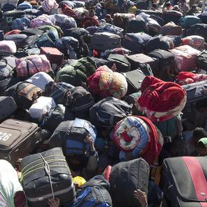 Refugees from Bangladesh carry their suitcases after crossing the Libya-Tunisia border (AP)
