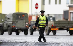A security officer patrols the entrance to the Massereene army barracks in Antrim, west of Belfast, Northern Ireland Sunday, March, 8, 2009 after two British soldiers were shot to death and four other people wounded in a drive-by ambush that politicians blamed on IRA dissidents. Suspected IRA dissidents who opened fire on British soldiers and pizza delivery men outside an army base shot their victims again as they lay wounded on the ground, police said Sunday. Two soldiers died and four other people, including two men delivering pizzas, remained hospitalized with serious wounds following Saturday night's attack at the entrance to Massereene army barracks in Antrim, west of Belfast.  (AP Photo/Peter Morrison)