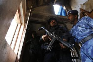 National Security Guard commandoes take position near an apartment where suspected gunmen have held a family hostage in Colaba, Mumbai, India, Thursday, Nov. 27, 2008. Teams of gunmen stormed luxury hotels, a popular restaurant, hospitals and a crowded train station in coordinated attacks across India's financial capital, killing at least 101 people, taking Westerners hostage and leaving parts of the city under siege Thursday, police said. A group of suspected Muslim militants claimed responsibility. (AP Photo/Saurabh Das)