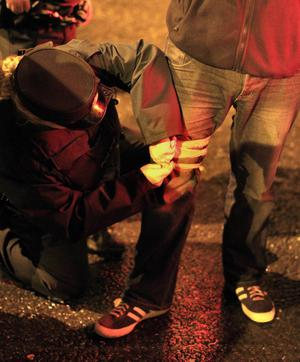 A PSNI officer puts a bandage on a press photographer's leg after he was shot by a rioter