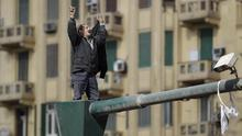 A man standing on lamppost and holding spent ammunition cartridges reacts on Tahrir, or Liberation Square, in Cairo, Egypt, Monday Jan. 31, 2011. A coalition of opposition groups called for a million people to take to Cairo's streets Tuesday to ratchet up pressure for President Hosni Mubarak to leave. (AP Photo/Ben Curtis)