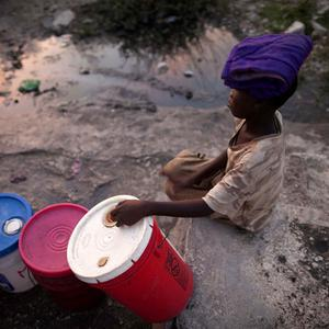 A boy waits to collect water to be used for cleaning or cooking at the Cite Soleil slum in Port-au-Prince, Haiti(AP)
