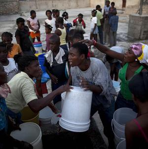 Residents argue while they wait to collect water to be used to clean and cook at the Cite Soleil slum in Port-au-Prince, Haiti(AP)
