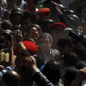 Egypt's new prime minister Essam Sharaf is surrounded by supporters as he arrives in Tahrir Square (AP)