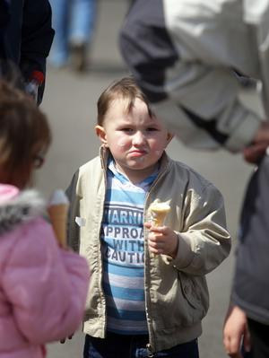 A child at the show eats ice cream in the warm sun