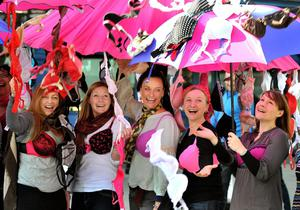 A large group of women including students from Oregon USA, appear to be caught in a downpour of women's bras at the launch of Oxfam's Big Bra Hunt in Spitalfields Market in east London.