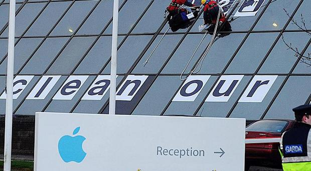 Gardai look on as Greenpeace activists scale the Apple HQ offices in Cork