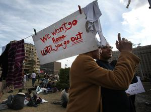 CAIRO, EGYPT - JANUARY 30:  Protestors stand under a placard in Tahrir Square on January 30, 2011 in Cairo, Egypt. Cairo remained in a state of flux and marchers continued to protest in the streets and defy curfew, demanding the resignation of Egyptian president Hosni Mubarek. As President Mubarak struggles to regain control after five days of protests he has appointed Omar Suleiman as vice-president. The present death toll stands at 100 and up to 2,000 people are thought to have been injured during the clashes which started last Tuesday. Overnight it was reported that thousands of inmates from the Wadi Naturn prison had escaped and that Egyptians were forming vigilante groups in order to protect their homes.   (Photo by Peter Macdiarmid/Getty Images)