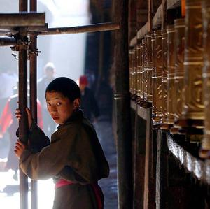 A young Buddhist monk stands near prayer's wheels at Jokhang Temple in Barkhor in Lhasa, Tibet, where two people set fire to themselves (AP)