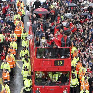 The Manchester United team celebrate with the Premier League trophy during an open top bus parade (AP)
