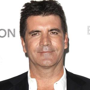 Simon Cowell has pledged to support X Factor colleague Louis Walsh 'one hundred per cent' amid allegations of assault