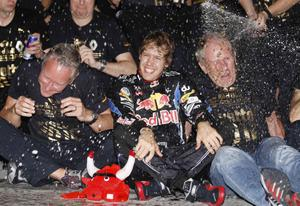Red Bull driver Sebastian Vettel of Germany , center, celebrates with team members in the Red Bull pit after becoming 2010 Formula One World champion and winning  the Emirates Formula One Grand Prix at the Yas Marina racetrack, in Abu Dhabi, United Arab Emirates, Sunday, Nov.14, 2010. (AP Photo/Luca Bruno)