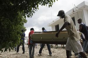 People carry a coffin containing the remains of a person who allegedly died from diarrhea in Saint Marc, Haiti, Thursday, Oct. 21, 2010. Health officials said an outbreak of severe diarrhea has killed at least 54 people and sickened hundreds more while patients have been lying on blankets outside the crowded hospital and doctors are testing for cholera, typhoid and other illnesses that could have caused the outbreak.(AP Photo/Dieu Nalio Chery)