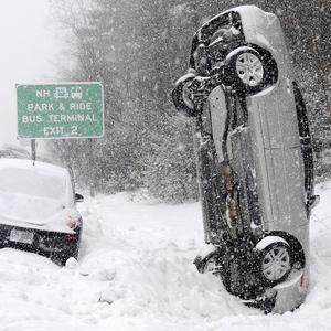 A car that left the road near Salem landed vertically in a snow drift with the occupants escaping uninjured (AP)