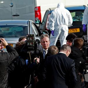 First Minister Peter Robinson, centre, speaking at the scene where police officer Ronan Kerr was killed