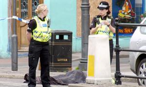 Police stand next to a body covered by a blanket  following a shooting on  Duke Street, Whitehaven, Cumbria,