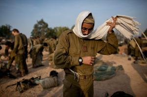 ISRAEL/GAZA BORDER, ISRAEL- NOVEMBER 19:  (ISRAEL OUT) An Israeli soldier prepares for morning prayers in a deployment area on November 19, 2012 on Israel's border with the Gaza Strip. The death toll has risen to at least 85 killed in the air strikes, according to hospital officials, on day six since the launch of operation 'Pillar of Defence.'  (Photo by Uriel Sinai/Getty Images)