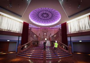 A technician walks up a replica of The Titanic's Grand Staircase at the Titanic Belfast attraction