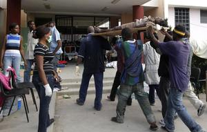 A victim is carried into the Hospital Universitaire de la Paix in Port-au-Prince, Thursday, Jan. 14, 2010