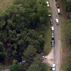 Authorities at a rural house in Texas after receiving a tip that multiple dismembered bodies were buried there (AP Photo/KPRC-TV)