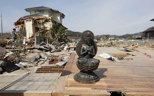 A statue is all that remains of a house in the seaside town of Toyoma, northern Japan, Monday, March 14, 2011, three days after a giant quake and tsunami struck the country's northeastern coast. (AP Photo/Mark Baker)