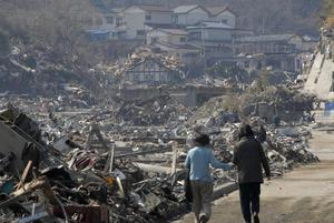 A couple walk along the rubble at a residential area in Onagawa, Miyagi Prefecture, northern Japan, Sunday, March 13, 2011, two days after a powerful earthquake-triggered tsunami hit the country's east coast. (AP Photo/The Yumiuri Shimbun) JAPAN OUT, CREDIT MANDATORY