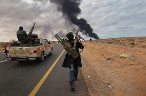 RAS LANUF, LIBYA - MARCH 09:  A rebel fighter carries of load of rocket propelled grenades while advancing on the frontline on March 9, 2011 near Ras Lanuf, Libya. The rebels pushed back government forces loyal to Libyan leader Muammar Gaddafi towards Ben Jawat.  (Photo by John Moore/Getty Images)