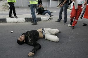 An injured Palestinian lies on the ground during a protest against the Israeli military operations in Gaza Strip near the West Bank city of Nablus, Sunday, Nov. 18, 2012. (AP Photo/Nasser Ishtayeh)
