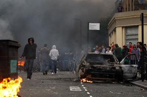 LONDON, ENGLAND - AUGUST 08:  Local residents and rioters look towards the police line from behind a burnt out car in Clarence Road in Hackney on August 8, 2011 in London, England. Pockets of rioting and looting continues to take place in various boroughs of London this evening, as well as in Birmingham, prompted by the initial rioting in Tottenham and then in Brixton on Sunday night. It has been announced that the Prime Minister David Cameron and his family are due to return home from their summer holiday in Tuscany, Italy to respond to the rioting. Disturbances broke out late on Saturday night in Tottenham and the surrounding area after the killing of Mark Duggan, 29 and a father-of-four, by armed police in an attempted arrest on August 4.  (Photo by Dan Istitene/Getty Images)