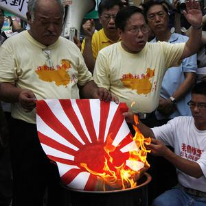 Anti-Japan protesters burn a rising sun flag of former Imperial Japanese military (AP)