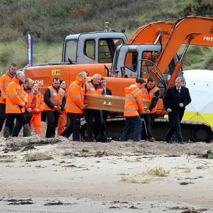 The remains of a body, believed to be that of Peter Wilson, are removed from Waterfoot beach in the Glens of Antrim