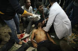 CAIRO, EGYPT - JANUARY 29:  Medics in a mosque attend to a man injured during clashes with riot police near Tahrir Square on January 29, 2011 in Cairo, Egypt. Tens of thousands of demonstrators have taken to the streets across Egypt in Cairo, Suez, and Alexandria to call for the resignation of President Hosni Mubarak. Riot police and the Army have been sent into the streets to quell the protests, which so far according to health officials have claimed at least 45 lives and left more than a two-thousand injured. The cabinet has formally resigned, but protesters are seeking a regime change with the resignation of Mubarak. Whilst the Army has deployed tanks and Armoured Personnel Carriers (APCs) to the streets there has been little implementation of them, and soldiers have interacted peacefully with passing marchers. The government has installed a curfew, blockaded access to the Giza pyramids with tanks and APC's and taken measures to secure museums from looters.  (Photo by Peter Macdiarmid/Getty Images) *** BESTPIX ***