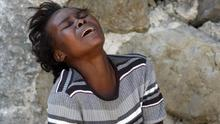 Elliane Garcon cries as she watches the body of her husband, Rene Morancy, being dumped from a front loader into a truck as crews remove bodies from the streets in the aftermath of Tuesday's earthquake in Port-au-Prince