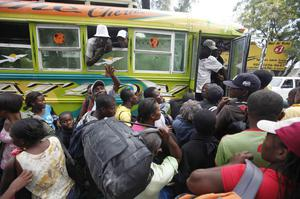 Haitians board a bus to leave Port-au-Prince, Haiti, Sunday, Jan. 17, 2010.